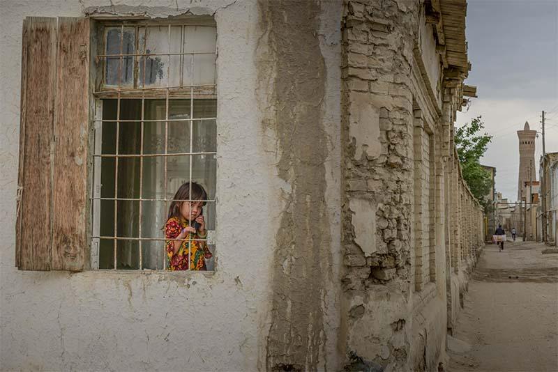Meisje kijkt uit raam in stadje in Oezbekistan